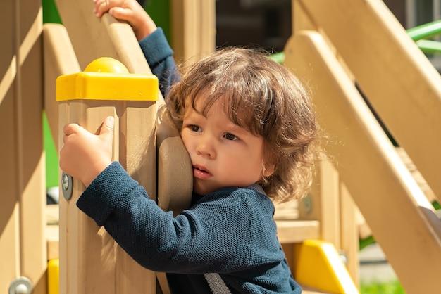 Porträt eines langhaarigen jungen, der es satt hat, auf dem spielplatz draußen auf der straße zu spielen?