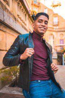 Porträt eines latino-jungen in der stadt. jeans, lederjacke und braune schuhe