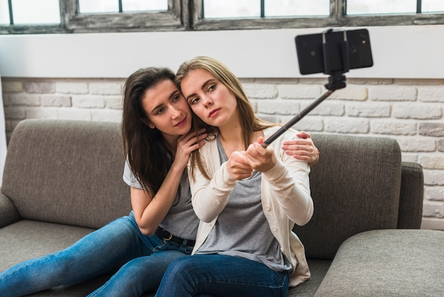 Porträt eines lesbischen jungen paares, das auf dem sofa nimmt selfie am handy sitzt