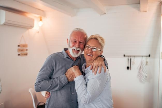 Porträt eines liebevollen älteren paares zuhause. umarmen, lächeln und blick in die kamera.
