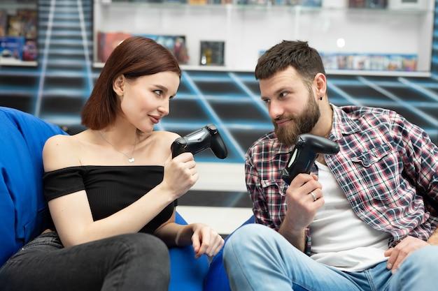 Porträt eines lustigen, aktiven paares, das videospiele auf der playstation mit einem konsolenspielfeld in der hand spielt, xbox-fans