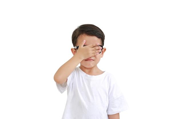 Porträt eines lustigen asiatischen kleinen jungen, der eine brille trägt und versteckte augen mit einer hand schließt, isoliert auf weißem hintergrund