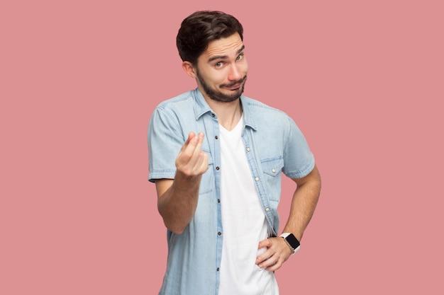 Porträt eines lustigen, gutaussehenden, bärtigen jungen mannes im blauen hemd im casual-stil, der mit geld oder italienischer geste mit der hand in die kamera steht und schaut. indoor-studioaufnahme, isoliert auf rosa hintergrund.