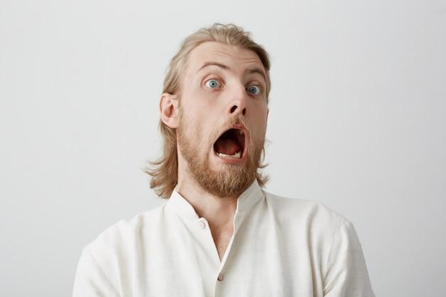 Porträt eines lustigen gutaussehenden bärtigen mannes mit hellem haar, der schock ausdrückt oder angst vor etwas hat