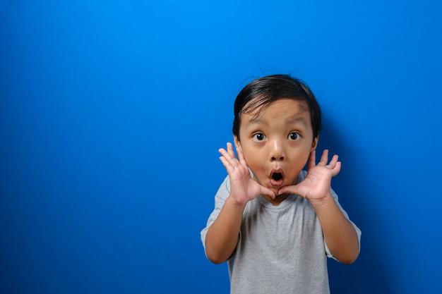 Porträt eines lustigen jungen asiatischen jungen, der die kamera mit großen augen betrachtet, die seinen mund bedecken, schockiert überraschter ausdruck vor blauem hintergrund