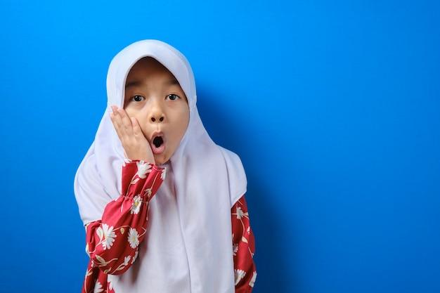 Porträt eines lustigen jungen asiatischen muslimischen mädchens, das die kamera mit großen augen betrachtet, die seinen mund bedecken, schockiert überraschter ausdruck vor blauem hintergrund