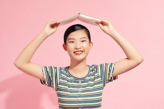 Porträt eines lustigen jungen lächelnden studentenmädchens mit einem offenen buch auf dem kopf über rosafarbenem hintergrund