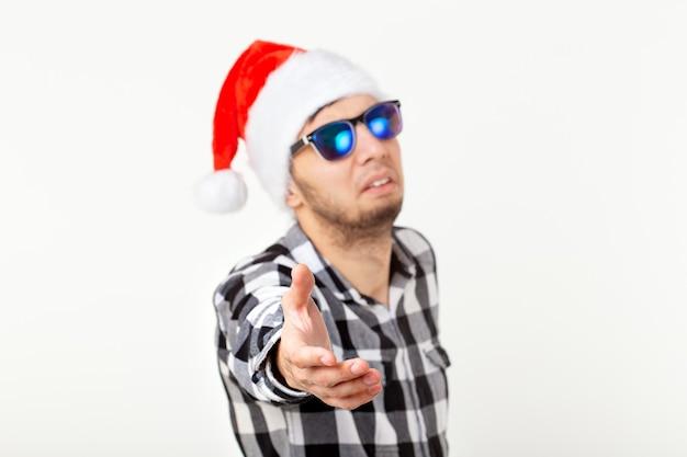 Porträt eines lustigen jungen mannes in santa claus-hut und bart auf weißem hintergrund. weihnachten.