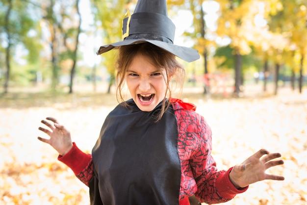 Porträt eines lustigen kleinen mädchens, das ein unheimliches gesicht mit einem schwarzen hexenhut aus papier macht, während es im herbstpark geht. halloween-meeting-konzept