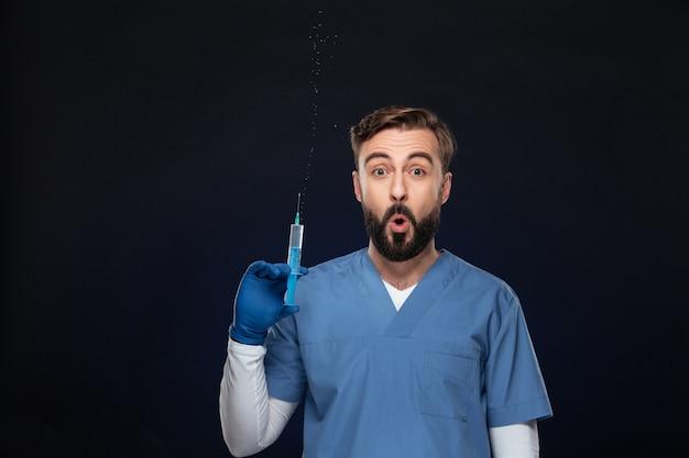 Porträt eines lustigen männlichen doktors kleidete in der uniform an