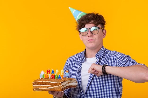 Porträt eines lustigen positiven kerls mit einer papierkappe und gläsern, die einen glückwunschkuchen in seinem halten