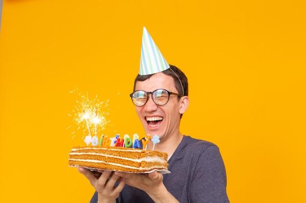 Porträt eines lustigen positiven kerls mit einer papierkappe und gläsern, die einen glückwunschkuchen in seinen händen auf einer gelben oberfläche halten
