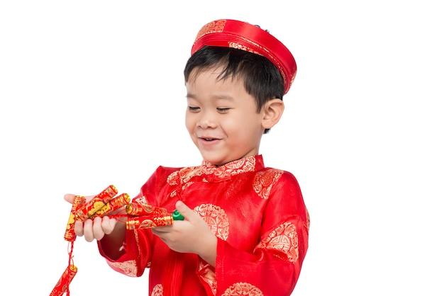 Porträt eines lustigen und aufregenden vietnamesischen jungen mit feuerwerkskörpern. asiatisches kind feiert neujahr