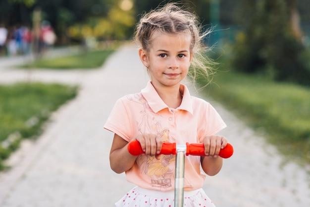 Porträt eines mädchens auf stoßroller im park