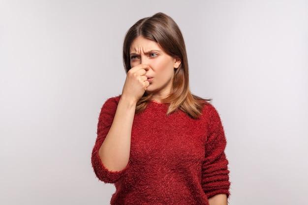 Porträt eines mädchens, das angewidert das gesicht verzieht und sich die nase kneift, verwirrt durch mundgeruch, stinkig