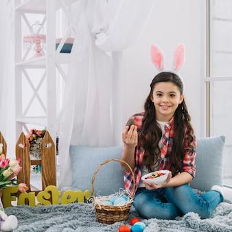 Porträt eines mädchens, das auf dem bett hält ostern-schokoladenei und schüssel süßigkeiten schauend zur kamera sitzt
