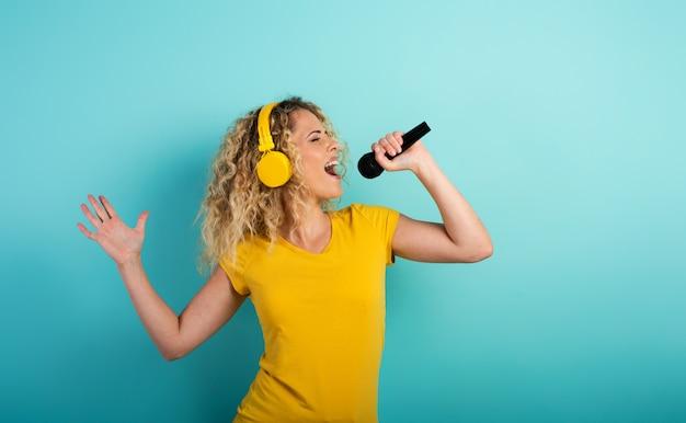 Porträt eines mädchens, das auf einem blauen hintergrund singt