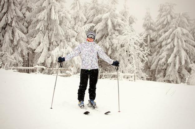 Porträt eines mädchens, das auf skiern steht und gegen schneebedeckte berge und wälder aufwirft. winternatur in den bergen der karpaten. frau ist skifahrerin. starker schneefall fällt.