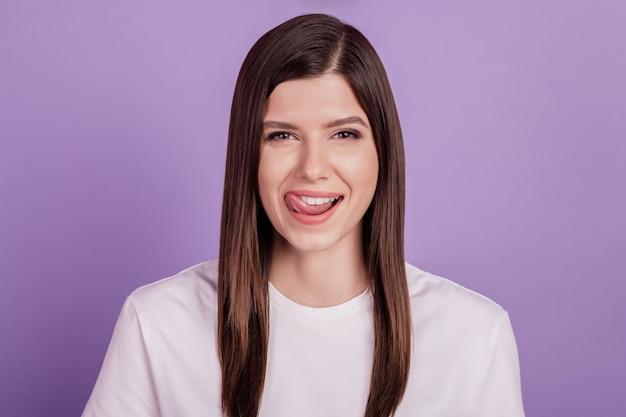 Porträt eines mädchens, das die weißen gesunden zähne der lippen leckt, die auf purpurrotem hintergrund lokalisiert werden