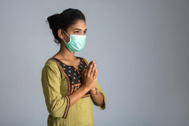 Porträt eines mädchens, das eine medizinische maske trägt, die gruß mit namaste-geste tut.