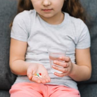 Porträt eines mädchens, das in der hand medizin und glas wasser hält