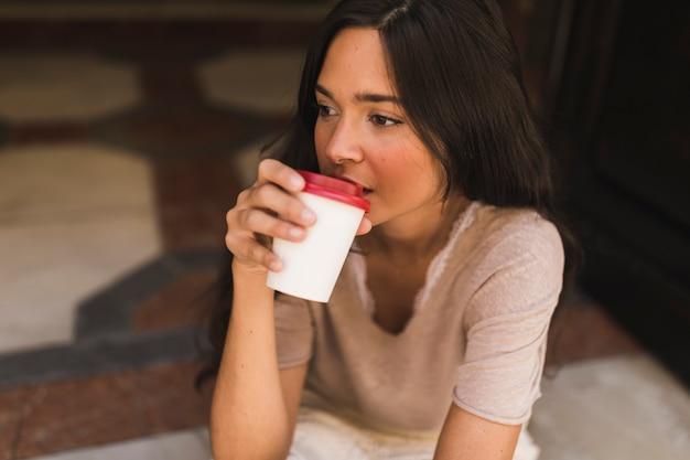 Porträt eines mädchens, das kaffee von der wegwerfschale trinkt