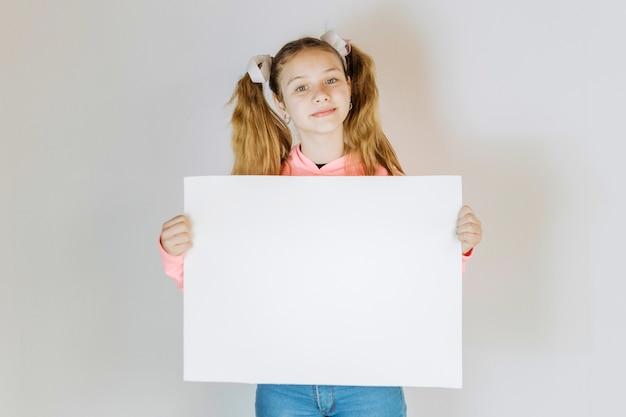 Porträt eines mädchens, das leeres weißes papppapier hält