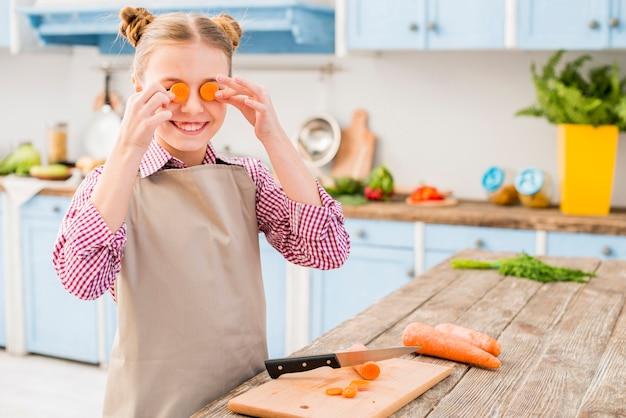 Porträt eines mädchens, das seine augen mit karottenscheibe in der küche bedeckt