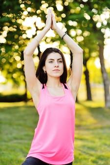 Porträt eines mädchens, das yoga auf grünem gras tut