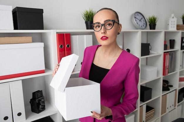 Porträt eines mädchens im geschäftsstil, das nach dokumenten in einer weißen box sucht