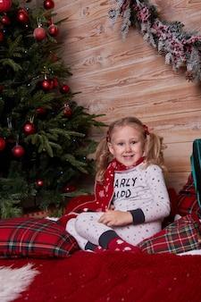 Porträt eines mädchens im pyjama, das auf dem bett unter dem weihnachtsbaum mit geschenken in geschenkboxen sitzt.