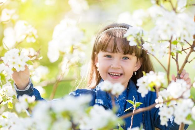 Porträt eines mädchens in blühendem apfelbaum.
