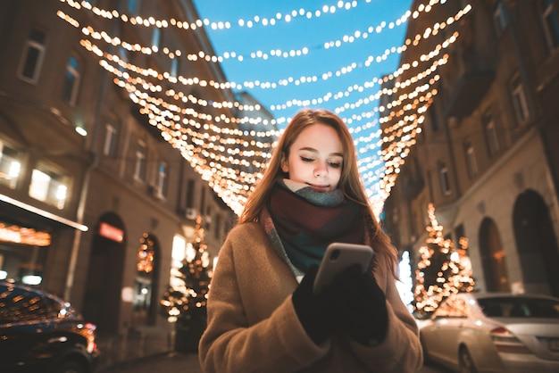 Porträt eines mädchens in der warmen kleidung, die draußen vor dem hintergrund der bokeh-lichter steht und ein smartphone verwendet