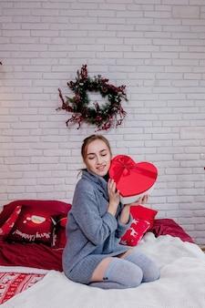 Porträt eines mädchens in einem grauen pullover mit einer herzförmigen roten geschenkbox. valentinstag