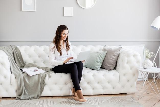 Porträt eines mädchens in einem hellen innenraum, ein mädchen von europäischem aussehen, das auf der couch sitzt, manager, freiberufler