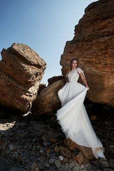 Porträt eines mädchens in einem herrlichen hochzeitskleid, das einen fotografen auf dem strand aufwirft. die braut ist auf den felsen