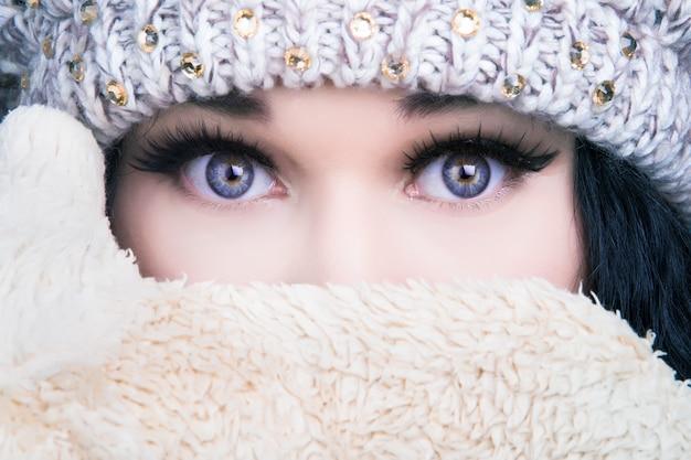 Porträt eines mädchens in einem hut und fäustlinge, die ihr gesicht bedecken, kaltes winterkonzept