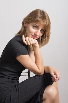 Porträt eines mädchens in einem schwarzen kleid, das auf einem stuhl sitzt