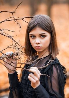 Porträt eines mädchens in einem schwarzen kleid in einem herbstlichen wald. eine junge hexe.