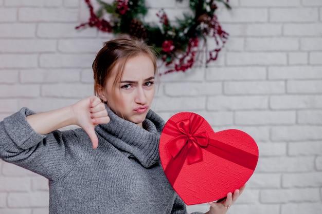 Porträt eines mädchens in einer grauen strickjacke mit einer herz-förmigen roten geschenkbox, die in der wohnung, valentinstagkonzept, kopienraum sitzt