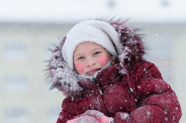 Porträt eines mädchens in einer roten daunenjacke. winter.