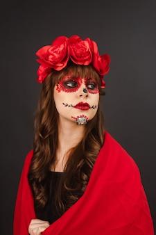 Porträt eines mädchens mit dia de los muertos make-up bedeckt mit einem roten umhang mit grauem hintergrund.