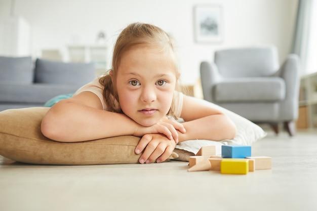 Porträt eines mädchens mit down-syndrom, das mit spielzeug und auf dem boden liegt