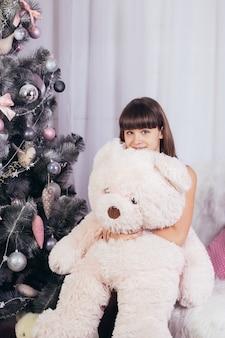 Porträt eines mädchens mit einem großen rosa spielzeugbären sitzt im hintergrund eines weihnachtsbaumes.