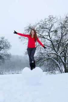 Porträt eines mädchens mit einem großen schneebedeckten herzen