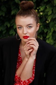 Porträt eines mädchens mit einem schönen make-up. roter lippenstift auf den lippen. sommerbild auf einer party