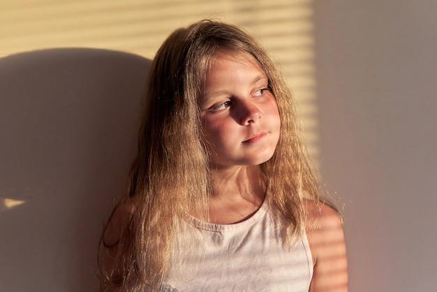 Porträt eines mädchens mit langen haaren, die von der sonne bei sonnenuntergang durch die jalousien beleuchtet werden.