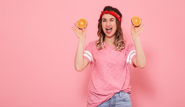 Porträt eines mädchens mit orangen in der hand, auf einer rosa wand