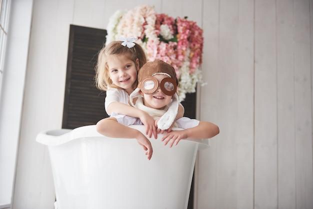 Porträt eines mädchens und eines jungen im pilotenhut, die im badezimmer bei piloten oder seeleuten spielen. das konzept von reisen, kindheit und verwirklichung von träumen