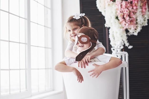 Porträt eines mädchens und eines jungen im versuchshut, der im badezimmer an den piloten oder an den seeleuten spielt. reisen, kindheit und die verwirklichung von träumen